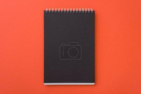 Foto de Vista superior de la espiral abierta cuaderno negro blanco l sobre fondo de escritorio naranja, lugar para el texto. - Imagen libre de derechos