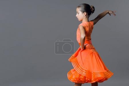 Photo pour Portrait d'une danseuse de 9-10 ans fille enfant. Sport danse de salon, latino. Jeune fille dans une robe orange sur un fond gris studio, espace copie - image libre de droit