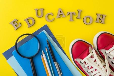 Photo for The concept of education. Red sneakers, school supplies, books, notebooks with yellow background. - Royalty Free Image