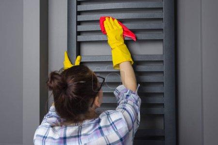 Foto de Mujer criada es limpieza. Limpia el calentador del baño con un trapo. - Imagen libre de derechos
