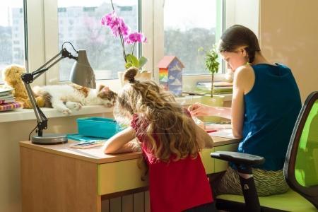 Photo pour Famille, loisirs, créativité, accueil. Sœurs filles à la maison à la table de peinture avec aquarelle. - image libre de droit
