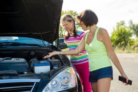 Photo for Woman driver with child on country road, near broken car. - Royalty Free Image