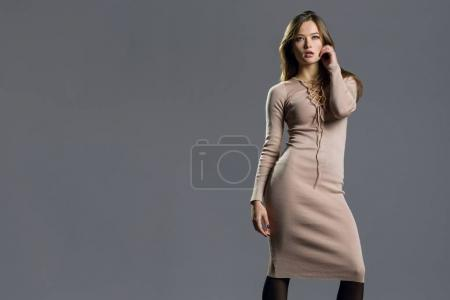 Photo for Beauty fashion model girl wearing stylish knitted dress. Sexy woman portrait with perfect makeup. Fashion blogger, grey background, copy space - Royalty Free Image