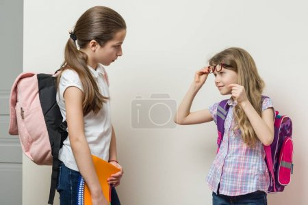 Photo for Communication of two girls at school. Schoolgirls with backpacks, background bright wall at school. - Royalty Free Image