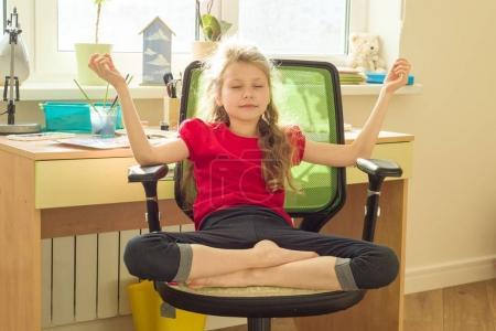 Photo pour Jeune fille médite à domicile sur une chaise près de la table de la fenêtre, dans une posture de lotus. - image libre de droit