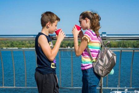 Photo pour L'heureux couple d'adolescents sont marcher, parler. Fond ville embankment, été - image libre de droit