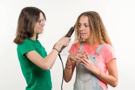 Foto de Retrato de dos amigas adolescentes haciendo el peinado en casa. Fondo blanco. - Imagen libre de derechos