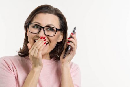 Photo pour Portrait d'une femme raconte les secrets et les potins sur le téléphone portable. Fond blanc, studio, espace copie. - image libre de droit
