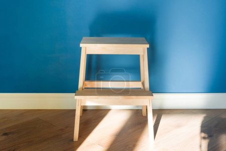 Photo for Wooden two step ladder stool with blue matte wall background. - Royalty Free Image