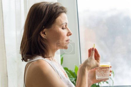 Photo for Woman takes pill with omega-3 and holding a glass of fresh water with lemon. Picture of the house, in the morning near the window. Vitamin D, E, a fish oil capsules. Nutrition, healthy eating, lifestyle - Royalty Free Image