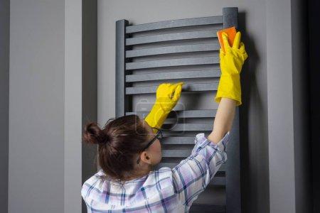 Photo pour La femme au foyer nettoie. Essuie le chauffage de la salle de bain avec chiffon . - image libre de droit