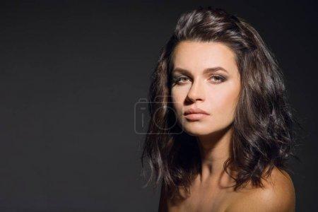 Foto de Cabello. Retrato de belleza de chica morena con el pelo ondulado brillante volumen. Mujer posando sobre fondo gris, mirando a cámara, espacio de copia - Imagen libre de derechos