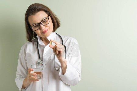 Photo pour Femme médecin prend la capsule de vitamine. Mode de vie sain, compléments alimentaires, vitamine d, e, capsules d'huile de poisson. Espace copie - image libre de droit