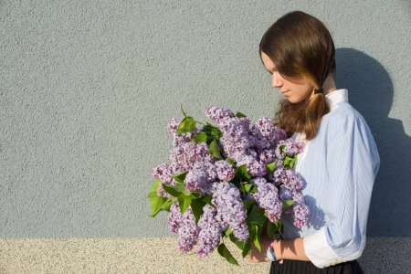 Photo for Profile portrait romantic teenage girl with bouquet of lilacs on gray wall background. Outdoor, copy space - Royalty Free Image