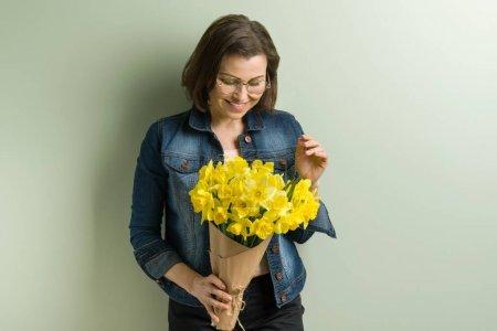 Photo pour Femme heureuse mature tenant bouquet avec des fleurs jaunes de printemps narcisse. Maisons, fond mur vert - image libre de droit