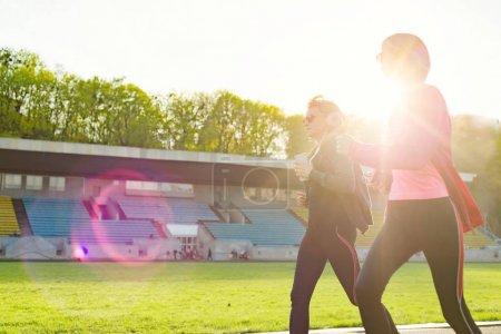 Photo pour Famille sport et fitness en plein air. Sportive mature mère et fille teen. Femme et fille sont courir dans le stade de la ville. Espace copie - image libre de droit