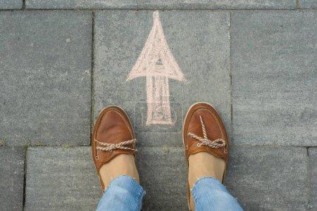 Photo pour Pieds femelles avec flèche peinte sur l'asphalte - image libre de droit