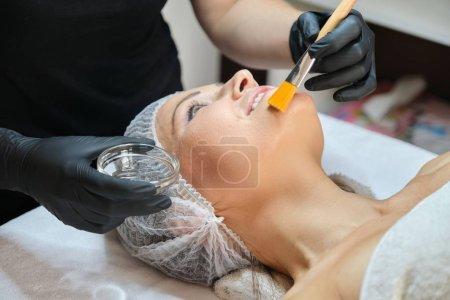 Photo pour Gros plan sur le visage de la femme mûre à l'âge cosmétique procédures dans le salon de beauté, les mains de l'esthéticienne avec brosse et cosmétique anti-âge sur le visage féminin - image libre de droit