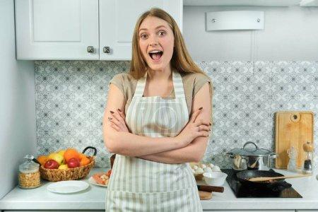Photo pour Jeune belle femme souriante en tablier aux bras croisés repliés, posant à la maison dans la cuisine, regardant la caméra, sur la table cuisine et nourriture - image libre de droit