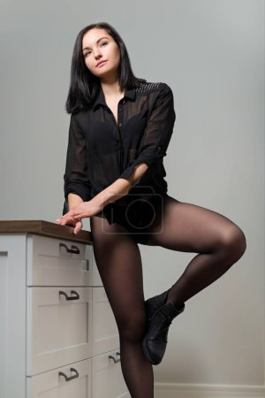Photo for Posing beautiful young woman in black nylon tights and stylish leather boots, female showing legs, shoe fashion - Royalty Free Image