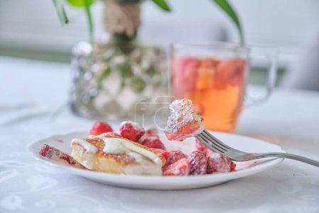 Photo pour Saison des fraises, nourriture et boisson avec des baies. Nourriture sur la table, crêpes caillées aux fraises et crème sure. Thé au citron et baies - image libre de droit