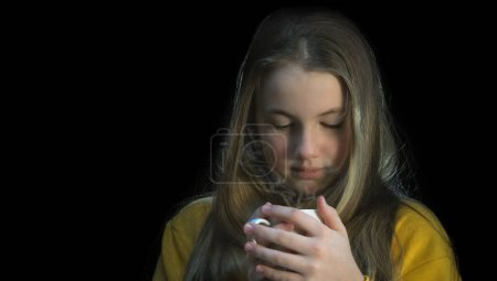 Photo pour Cute Girl holds a hot mug of drink in her hands. Isolated on black background - image libre de droit