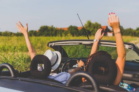 young women in cabriolet traveling