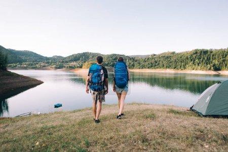 couple with backpacks  beside lake