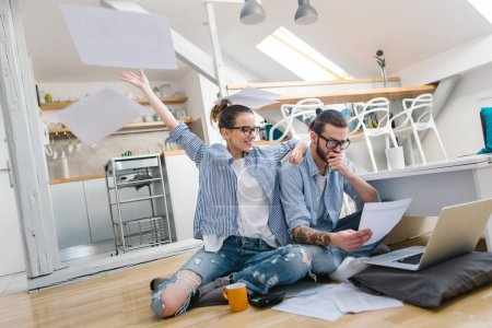 Photo for Happy young Couple checking bills at home - Royalty Free Image