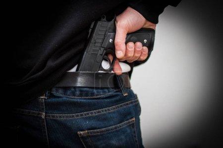 Photo pour L'homme caché le pistolet derrière leur dos, le vol, le crime, enlèvement - image libre de droit