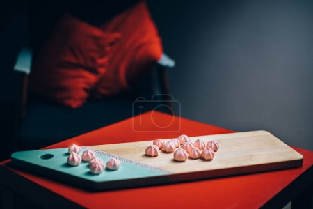 Pink marshmallows on cutting board in room