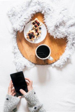 Photo pour Vue de dessus de jeune fille à l'aide de téléphone portable et de boire le café avec croissant et pain aux raisins secs sur le plateau en bois - image libre de droit