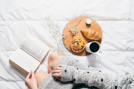 Photo pour Vue de dessus de fille lecture livre et boire le café avec croissant et pain aux raisins secs sur le plateau en bois - image libre de droit