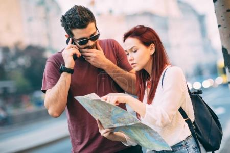 Couple of travelers using map in city