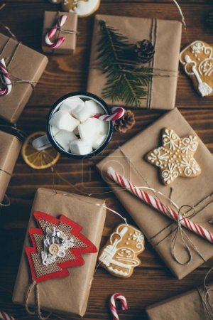 Cup of hot chocolate with marshmallows on wooden table with Christmas gifts