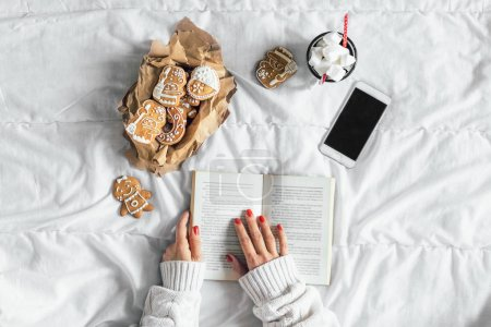 Photo for Woman reading book. Top view. Smartphone, hot chocolate  with marshmallows and cookies on white sheet - Royalty Free Image