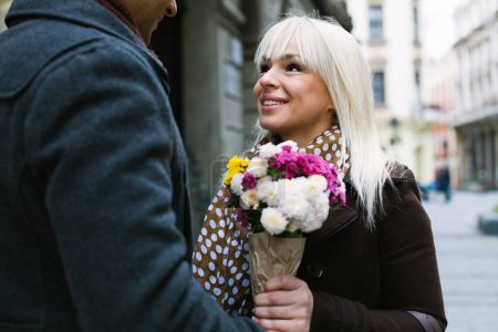Man gives flowers to his beutiful girlfriend on a date