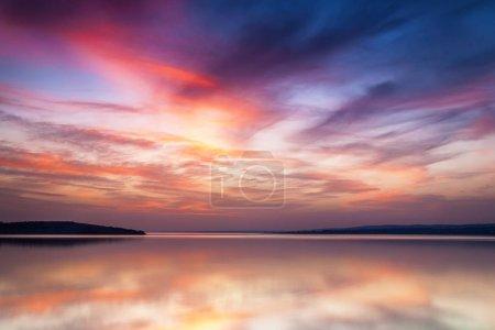 Photo pour Reflet d'un ciel coloré dans un lac au coucher du soleil - image libre de droit