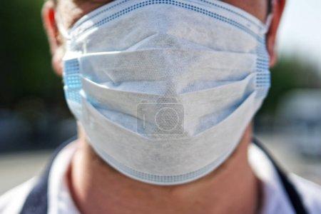 Photo pour Un homme en masque de protection se tient debout dans une rue de la ville. Protection antivirale. Pandémie, épidémie et médecine. Profondeur de champ peu profonde. Sans visage. - image libre de droit