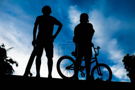 Photo for Rear view of two young man bmx bike and skateboard - Royalty Free Image