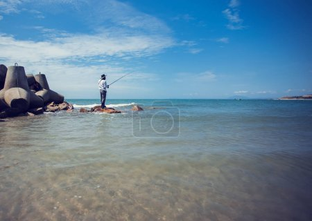 Photo for Fisherman fishing in the beach sunny day - Royalty Free Image