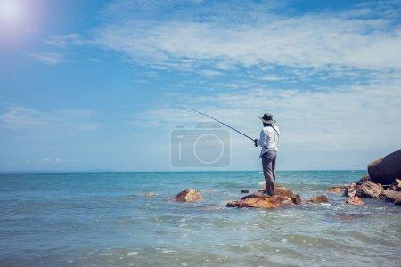 Photo pour Pêcheur pêche à la plage journée ensoleillée - image libre de droit