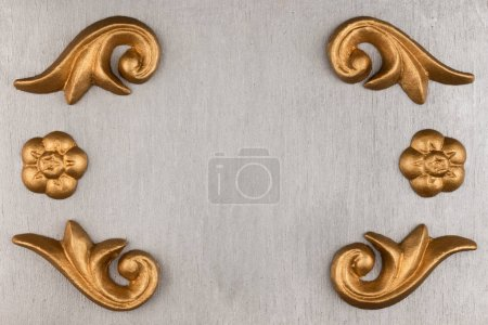 Luxury frame made of golden stucco plaster lying on silver surface