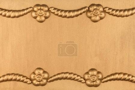 Luxury frame made of golden stucco plaster lying on gold surface