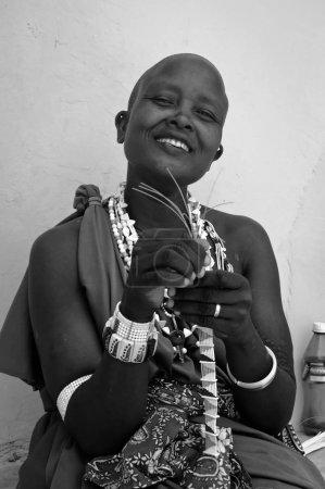 Photo pour Zanzibar, Kiwengwa - 19 janvier 2015: un portrait de jeunes belles femmes Massaï vêtues de robes traditionnelles et réaliserons, assis et le tissage traditionnel local bijoux - image libre de droit