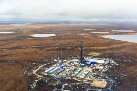 Photo pour Appareil de forage et équipement dans un champ pétrolifère de la toundra du Nord. Vue de dessus depuis un hélicoptère. Toundra d'automne avec lacs au-delà du cercle polaire arctique . - image libre de droit