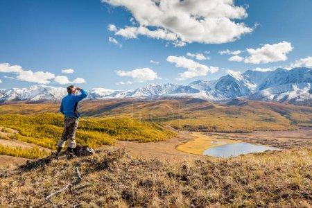 Man looking at Mountains and Lake