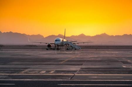 Airplane in the Evening Against the Backdrop of the Mountains