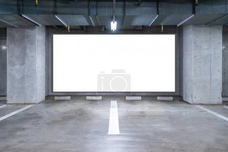 empty Parking garage underground with blank billboard, interior shopping mall at night