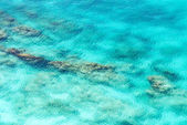 Top view of transparent shallow turquoise ocean sea water surface and rock at Andaman sea Indian ocean in summer.